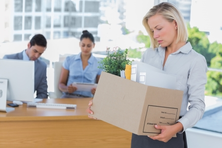 unemployed dismissed: Sad businesswoman leaving office after being let go holding box of belongings