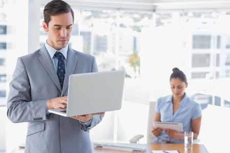 Businessman using laptop standing in office with woman working behind him Stock Photo - 20635693