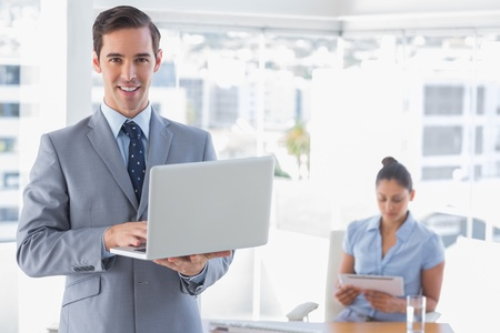 Businessman using laptop standing in office smiling at camera with woman working behind him photo