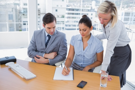 Businesswoman showing colleagues something on her notepad at desk in office