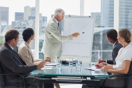 Businessman pointing at a growing chart during a meeting with people listening to him photo