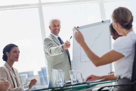Cheerful boss pointing at a colleague during a meeting
