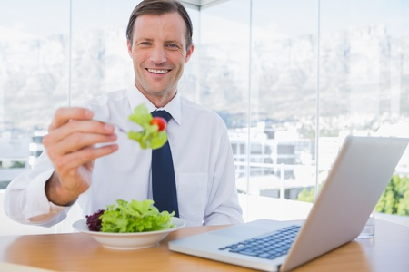 Smiling businessman eating a salad during the lunch time photo