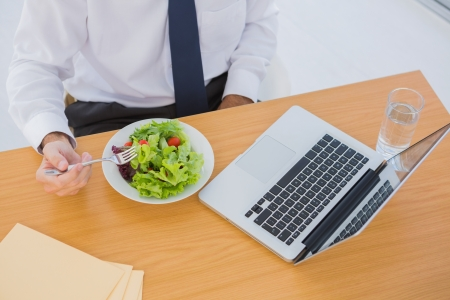 Overhead of a businessman eating a salad on his desk during the lunch time photo