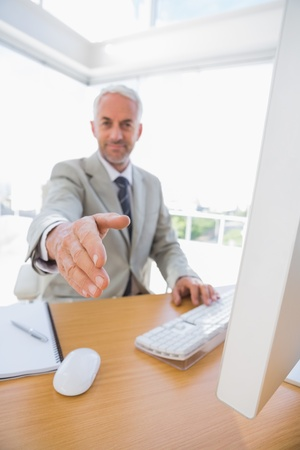 Cheerful businessman reaching hand out for handshake at his desk Stock Photo - 20635098