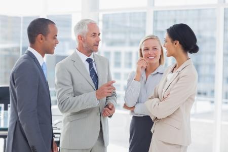 amigas conversando: Equipo de negocios feliz hablando juntos en la oficina