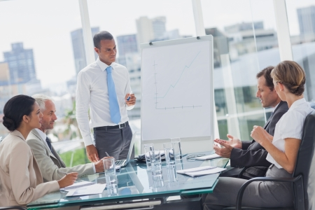 presenting: Manager standing in front of colleagues during a meeting Stock Photo