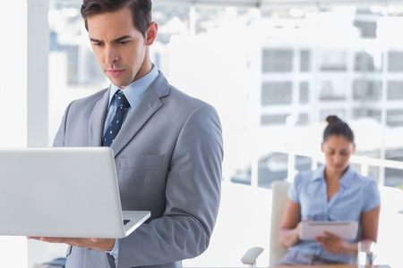 Businessman standing with laptop with woman working behind him Stock Photo - 20636857