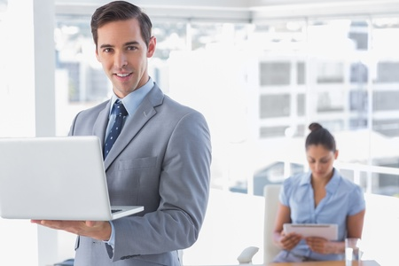 Businessman standing with laptop and smiling at camera with woman working behind him photo