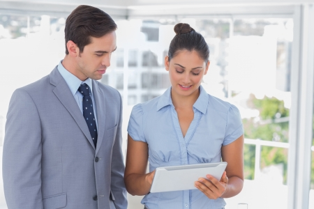 Business team looking at tablet pc together in the office Stock Photo - 20637822