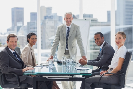 patron: Personas alegres de la gente de negocios en la sala de reunión con el jefe de pie en el medio