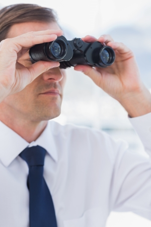 foresight: Serious businessman looking at the future with binoculars Stock Photo
