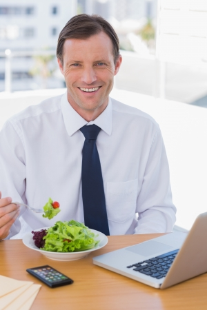 Cheerful businessman eating a salad on his desk during the lunch time photo