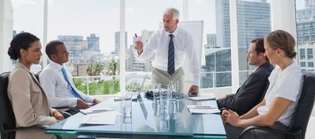 Boss gebaren in de voorkant van collega's tijdens een vergadering Stockfoto