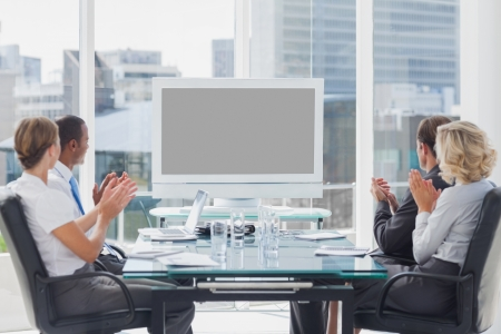 meeting business: Business people applauding at a screen during a video conference