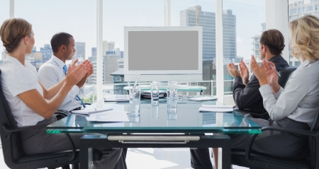 boardroom meeting: Business people applauding during a video conference in the boardroom Stock Photo