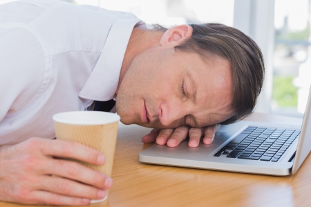 Businessman having a nap on his laptop while he is holding a cup of coffee Фото со стока - 20668317