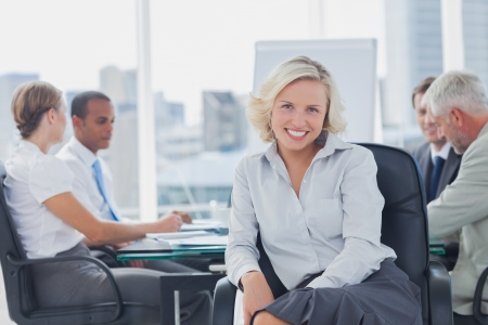 facing to camera: Attractive businesswoman posing in the boardroom with colleagues discussing behind Stock Photo