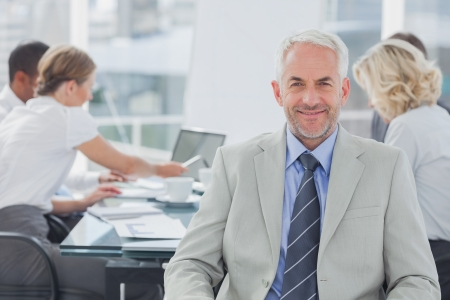 Boardroom meeting: Charismatic businessman posing in the boardroom while colleagues are working behind