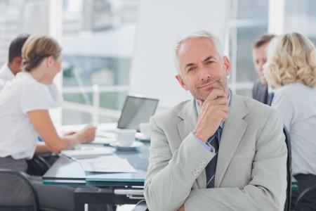 Sourire homme d'affaires posant dans la salle de réunion tandis que leurs collègues travaillent derrière Banque d'images