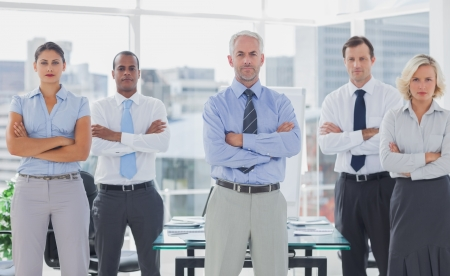 Team of business people standing with arms folded in the boardroom photo