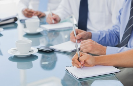 Boardroom meeting: Business people hands taking some notes during a meeting