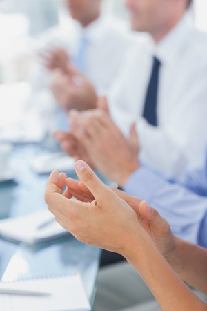 Boardroom meeting: Business people applauding together during a meeting Stock Photo