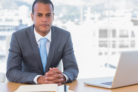 Handsome businessman posing at his desk in his office photo