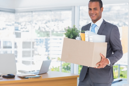 hopefulness: Smiling businessman leaving his company as he has been fired Stock Photo