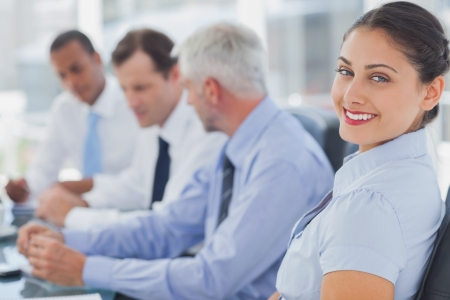 Boardroom meeting: Attractive businesswoman posing in the meeting room with colleagues working next to her
