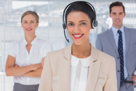 Attractive woman with headset standing in front of business team photo