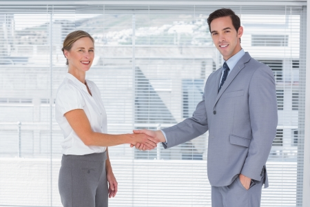 by hand: Two colleagues shaking hands in the office