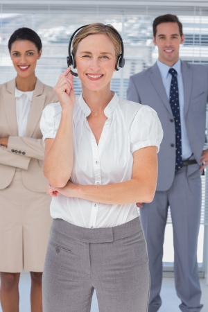 Cheerful woman with headset standing in front of smiling business people photo