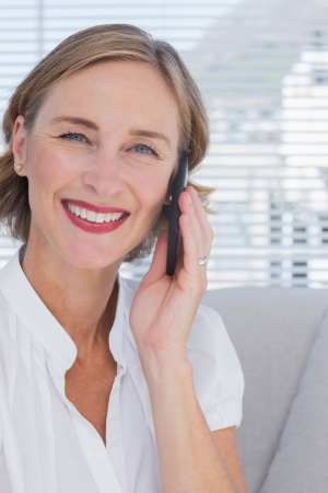 Portrait of businesswoman talking on phone in bright office photo