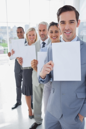 Business team in a line holding white pages smiling at camera photo