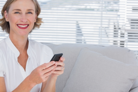 Smiling businesswoman using her mobile phone in bright office photo
