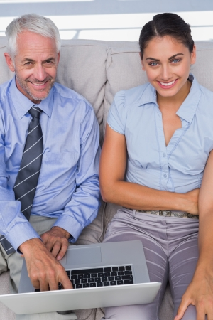Business people using laptop on the couch and smiling up at camera in the staffroom photo