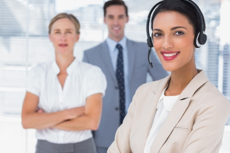 Attractive woman with headset crossing her arms in front of two business people photo