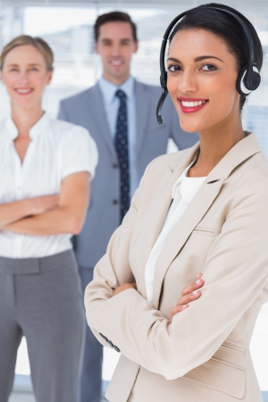 Smiling businesswoman with headset crossing her arms in front of two business people photo