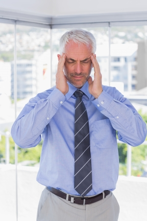 Stressed businessman rubbing his temples with eyes closed standing in his office photo