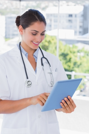Pretty young doctor using tablet pc and smiling by large windows photo