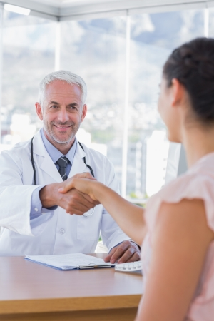 Patient shaking hands to doctor in the office at desk photo
