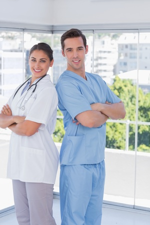Cheerful medical staff standing with arms folded photo