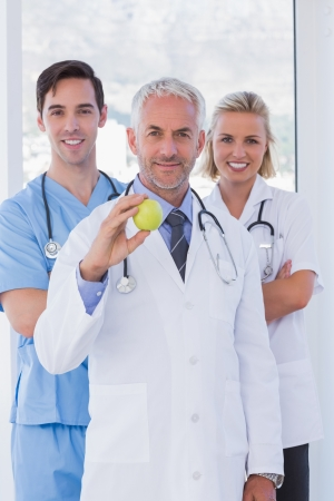 Cheerful medical staff standing together while one is holding a green apple photo
