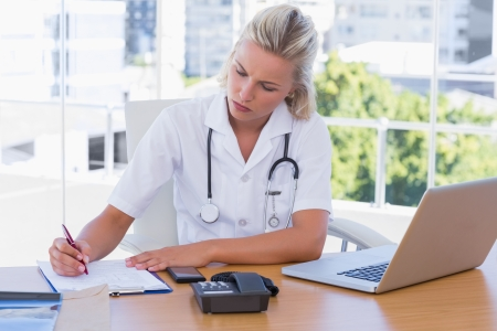Attractive nurse working in her office writing on a notepad photo