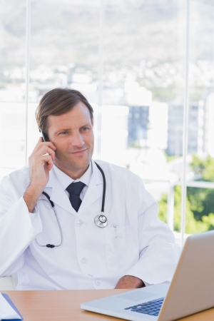 Cheerful doctor phoning in his modern office photo