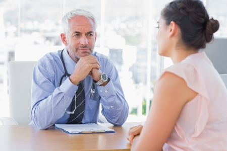 consulting: Concentrated doctor listening to patient in his office Stock Photo