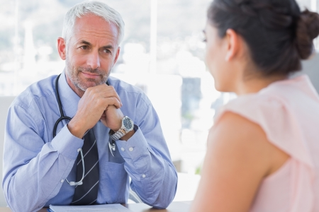 happy patient: Serious doctor listening to patient explaining her painful in his office Stock Photo