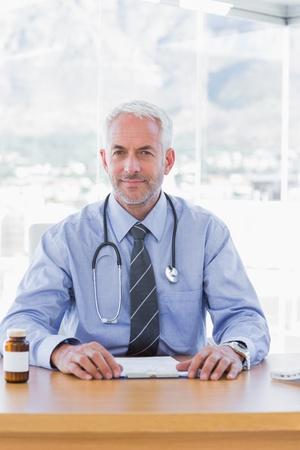 Handsome doctor sitting behind his desk photo