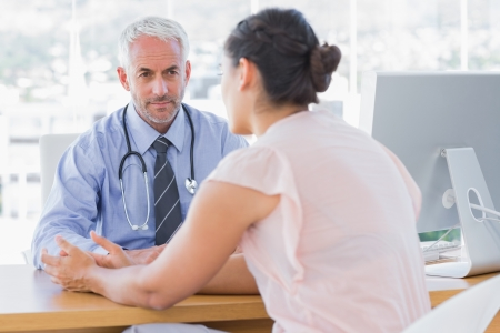doctor patient: Patient explaining her painful to doctor in the office